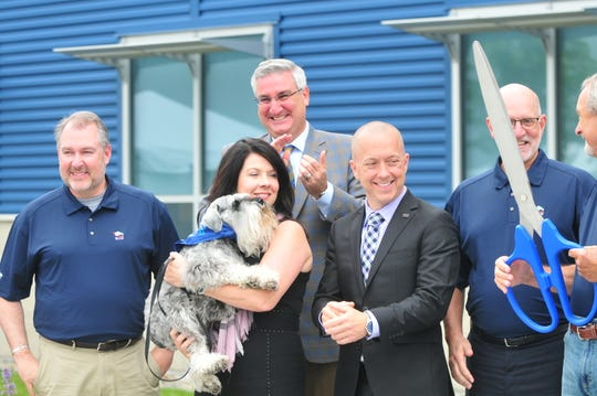 John R. Church (from left), Janet Holcomb (holding Henry), Gov. Eric Holcomb, Mayor Dave Snow and Jeffrey Harmening cheer after Bill Bishop cut the ceremonial ribbon Monday, June 17, 2019, at Blue Buffalo.