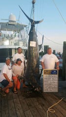 The crew of the Ocean City-based Top Dog poses next to their record-breaking 914-pound catch at the 61st Big Rock Blue Marlin Tournament.