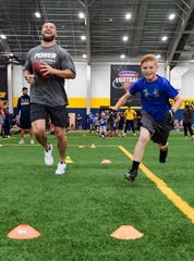 Philadelphia Eagles linebacker Nate Gerry races Dawson Bauer during a drill at a youth football camp Monday, June 17, at the Sanford Fieldhouse in Sioux Falls.