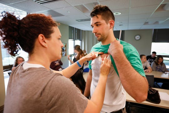Kaylee Weeks, a simulation coordinator at Ozarks Technical College, applies makeup to Louis Jones' chest to make it look like he received a gunshot wound as part of active shooter training at Cox South Medical Center on Monday, June 17, 2019.