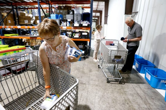 Volunteers Kathleen Greene (left) Bill Ricketts (right) and Deborah Nasbitt restock clothes for Care to Learns Mobile Clothing Closet at the Crosslines warehouse on Thursday, June 13, 2019.