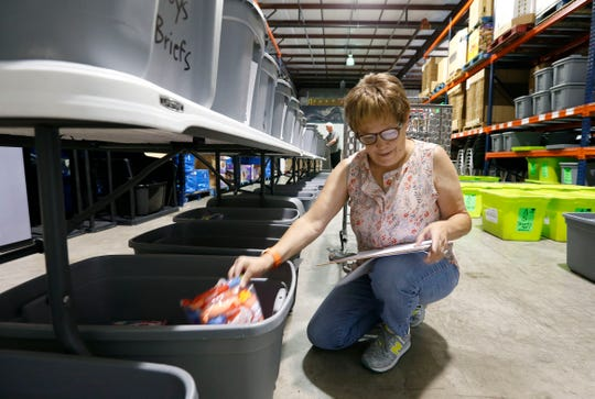 Volunteer Kathleen Greene restocks clothes for Care to Learns Mobile Clothing Closet at the Crosslines warehouse on Thursday, June 13, 2019.