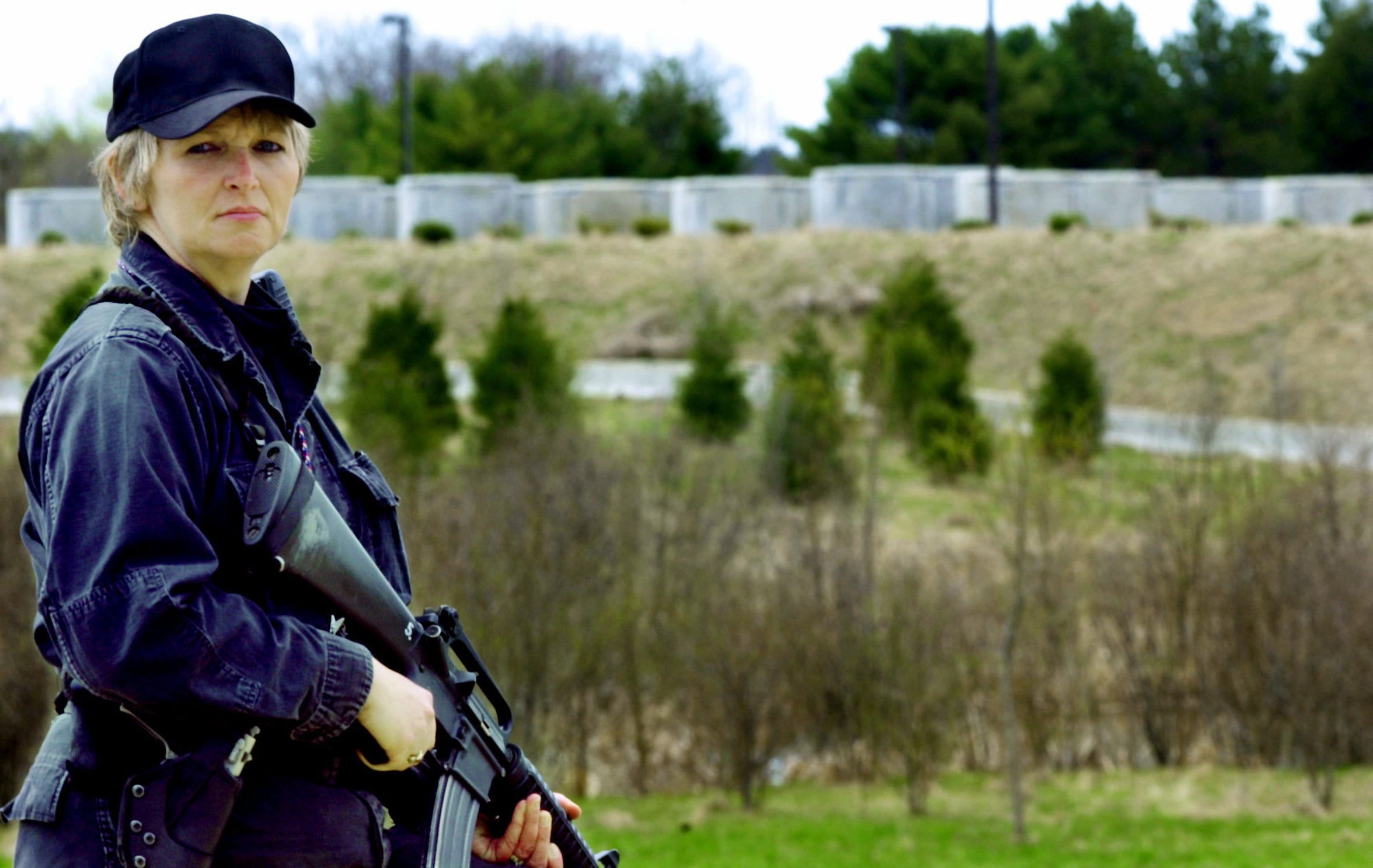 Theresa White of Gardiner, Maine, a security specialist at the former Maine Yankee nuclear power plant stands guard in Wiscasset, Maine, on Thursday, May 5, 2005. Spent fuel rods are stored in steel and concrete containers in the  background.