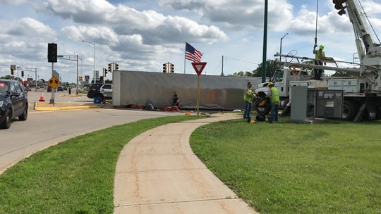 Semi blocks part of East Riverview Expressway Monday afternoon as workers try to tip it back on its wheels.
