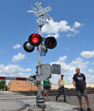 Pedestrians work to beat an oncoming train at the 7th Street railway crossing near downtown Wichita Falls. City leaders will look into an ordinance that would make it illegal for a pedestrian to walk in front of, under, or between rail cars that are moving or stationary at a grade crossing.