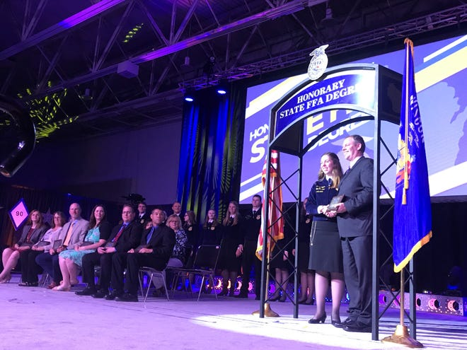 2018-19 Wisconsin FFA officer team president Amelia Hayden presents Luke Wiedenfeldwith an Honorary State FFA degree. He was among 13 recipients recognized for their dedication to youth leadership development.