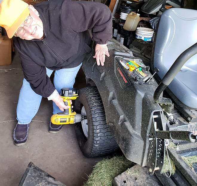 Susan tightens the lug nuts on a lawn mower tire.