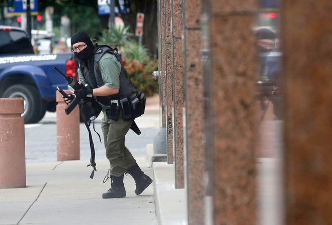 An armed shooter stands near the Earle Cabell Federal Building on Monday in downtown Dallas. The shooter was hit and injured in an exchange of gunfire with federal officers outside the courthouse.