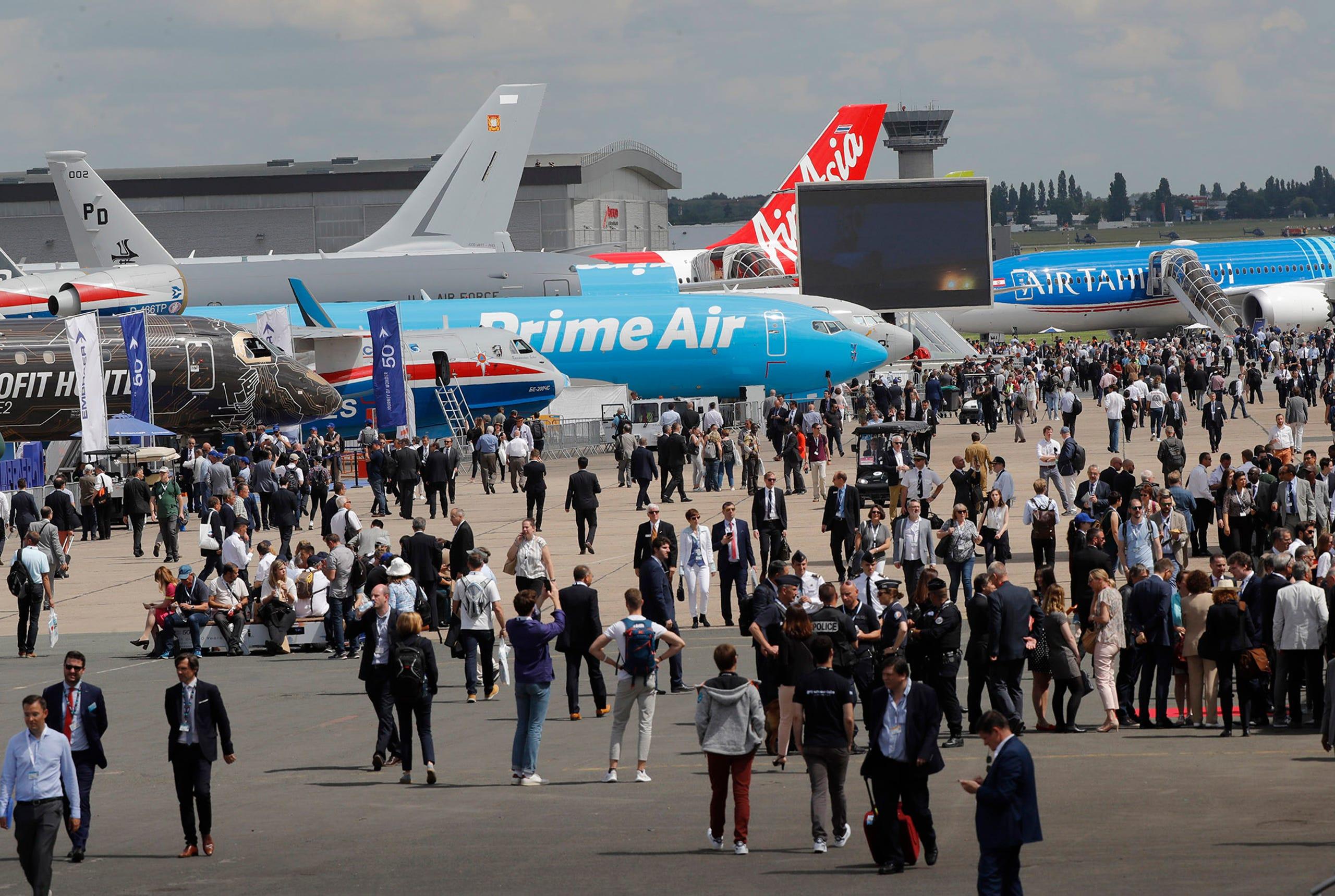 Visitors walk on the tarmac at the Paris Air Show, June 17, 2019.