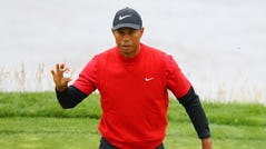 Tiger Woods salutes the crowd on the eighth green.