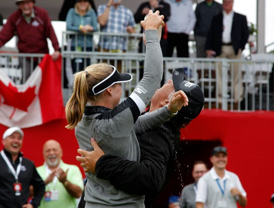 Brooke Henderson, left, pours champagne on her father, Dave, after winning the Meijer LPA Classic.