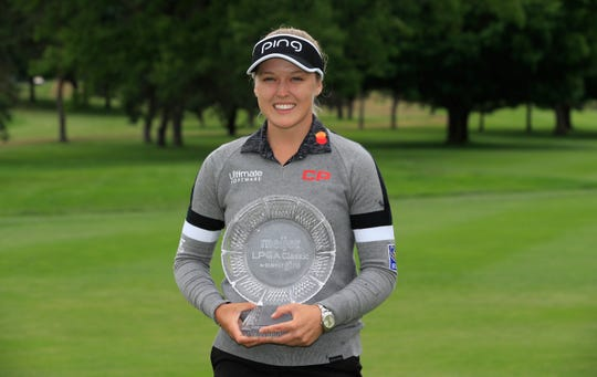 Brooke Henderson holds the winner's trophy after winning the Meijer LPGA Classic at Blythefield Country Club.