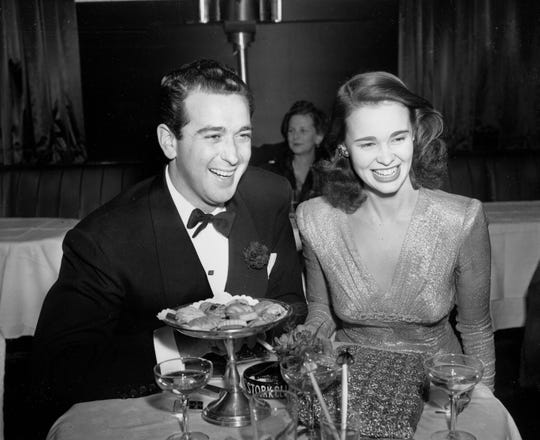 """Gloria Vanderbilt, 17-year-old heiress to the $ 4,000 000 fortune of her late father, Reginald Vanderbilt, celebrates her engagement to Pasquale """"Pat"""" Di Cicco, a Hollywood actor's agent, at New York's Stork Club, December 12, 1941. Gloria's mother, Mrs. Gloria Morgan Vanderbilt, announced that the couple will marry on Christmas Day in California.  (AP Photo)"""