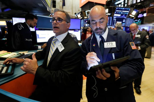 In this June 6, 2019, file photo specialist Anthony Rinaldi, left, and trader Fred DeMarco work on the floor of the New York Stock Exchange.