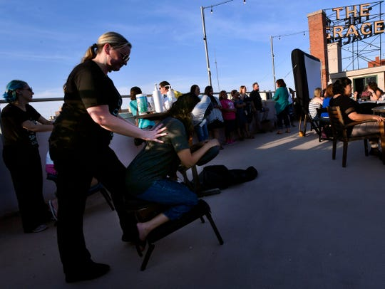 Leslie Ivey from Absolute Perfection Day Spa gives a massage Thurday during Teacher Appreciation Night on the roof of The Grace Museum Thursday. Teachers received free back rubs, snacks and drinks before the evening's movie.