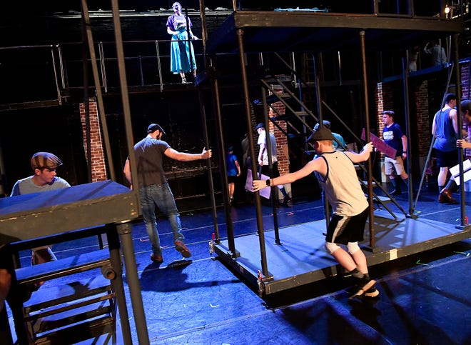 "Cast members move stair towers across the stage at the Paramount Theatre during a rehearsal for ""Newsies"" on Monday. The three-performance run opens June 28."