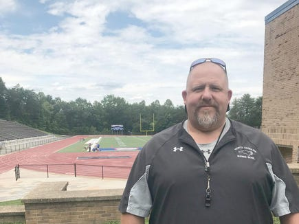 New McDowell Titans head football coach Darrell Brewer stands beside the fieldhouse at Titan Stadium last Wednesday afternoon. The 48-year-old former Avery head coach becomes the ninth different coach in McDowell High history.
