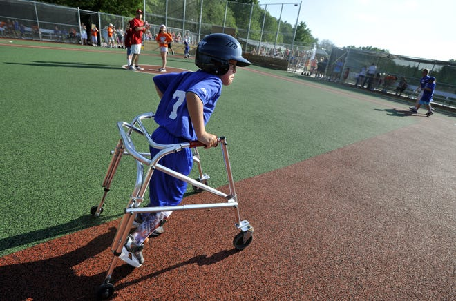 Jack Stoner of the Cubs wheels to third on the rubberized field during a Miracle League of Mid-Michigan game at the special Case Cares Miracle Field in DeWitt Township Wednesday, June 20, 2012.