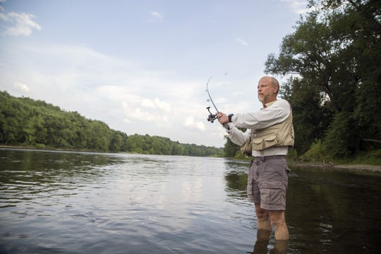 Richard Ferro, of Greene, casts his line into the Chenango River at a fishing spot in Otsiningo Park in August of 2015.