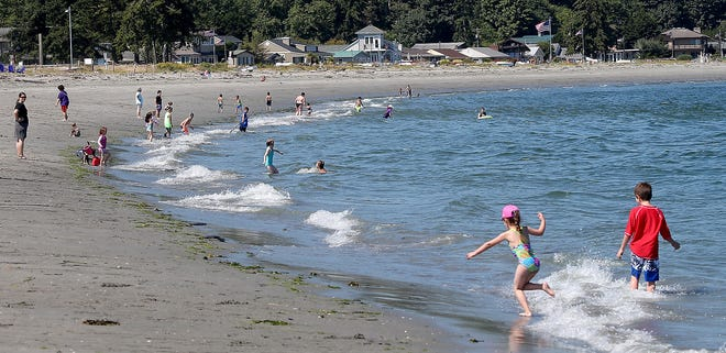 Youngsters dot the shoreline as the waves hit the beach at Point No Point in Hansville in July 2018.