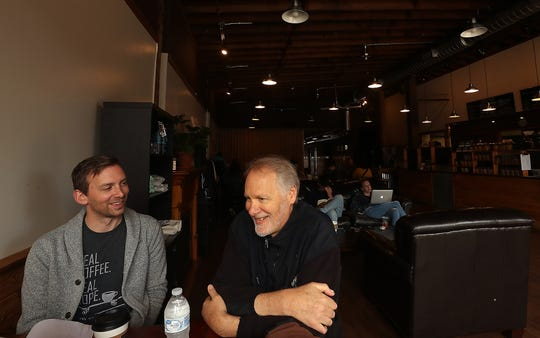 Daniel Frederick, left, smiles as his father, Dave, talks about what led him to start Coffee Oasis while the two sit in the Bremerton location. Daniel is the interim executive director, in line to take over the business as his father deals with the diagnosis of mesothelioma.