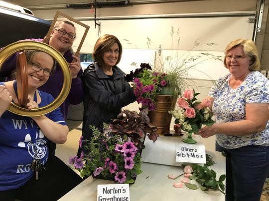 "The Earth, Wind and Flowers Garden Club members have been preparing their flower tribute to the Bucyrus Historical Society as it nears its 50th year. From left, Julie Rexroad and Amy Vaughn ""clown"" with frames to honor Henry's Studio, Sarah Kalb puts together her planter honoring Norton's Greenhouse and Flower Shop, and Karen Scott assembles a mound design in vintage glassware for Ulmer's Gifts and Music store. ""Downtown Bucyrus: Reminiscing 50 Years"" will be open from 11 a.m. to 3 p.m. Saturday, and noon to 4 p.m. Sunday at 202 S. Walnut St. During the free event, hostesses from the garden club and board members of the historical society will be on hand to celebrate visitors' memories and offer the opportunity to tour the home and grounds."