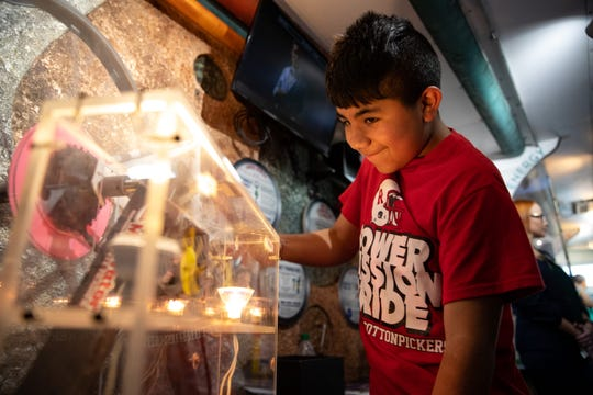 Robstown ISD student Joe Vallejo cranks a bicycle to power a light on the Texas Alliance for Minorities in Engineering's museum-on-wheels on Tuesday, June 18, 2019.