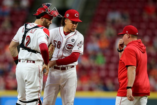 Cincinnati Reds pitching coach Derek Johnson (36), right, visits the mound to talk to Cincinnati Reds starting pitcher Luis Castillo (58), center, and Cincinnati Reds catcher Curt Casali (12) in the fourth inning of an MLB baseball game against the Houston Astros, Monday, June 17, 2019, at Great American Ball Park in Cincinnati.