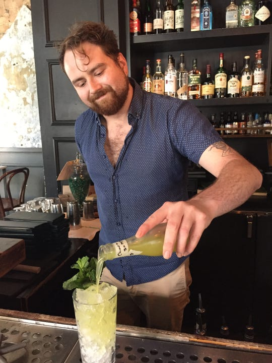 Aaron Kirby, assistant General Manager at Comfort Station pours a bottled cocktail, a chartreuse swizzler