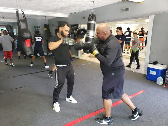 Cincinnati police Officer Donald Jordan (right) spars with a partner at Carradine Youth Boxing Academy on Friday, June 14, 2019.