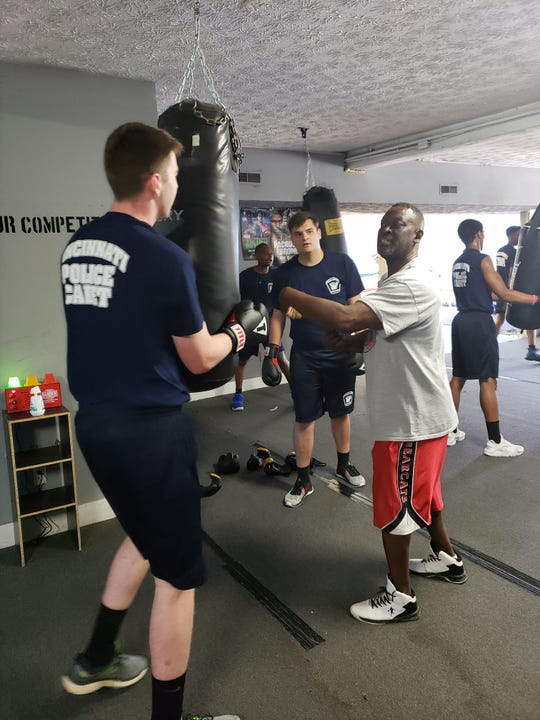 Jesse Carradine (right), owner of Carradine Youth Boxing Academy, shows members of the Cincinnati Police Cadet Academy proper boxing technique on Friday, June 14, 2019.