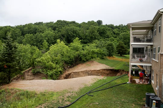 As a result of widespread rain, a sink hole formed behind a condo development , Tuesday, June 18, 2019, in Harrison.