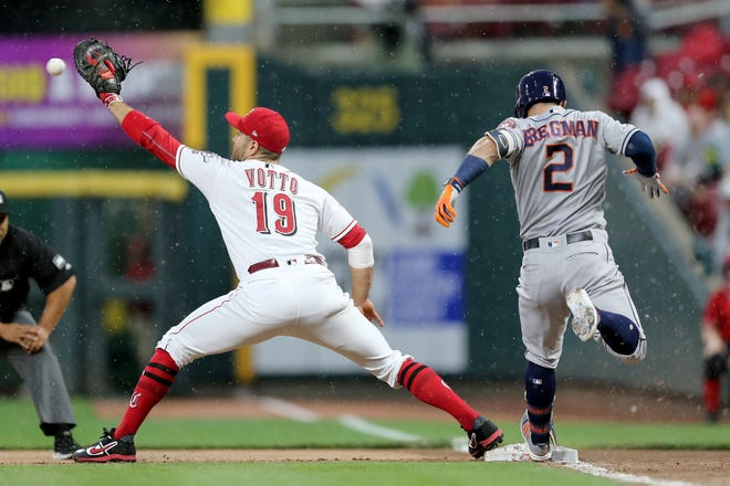 Houston Astros shortstop Alex Bregman (2) is called out at first base in the third inning as Cincinnati Reds first baseman Joey Votto (19) receive the throw of an MLB baseball game, Monday, June 17, 2019, at Great American Ball Park in Cincinnati.