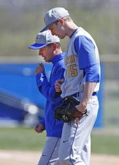 Newport Central Catholic High School coach Jeff Schulkens, rear, talks with pitcher Tommy Donnelly during a 2014 game.