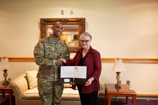 Staff Sgt. Michael Howard, APSU military science instructor and Army National Guard recruiter, and APSU President Dr. Alisa White hold the Tennessee STRONG Act deferment agreement.
