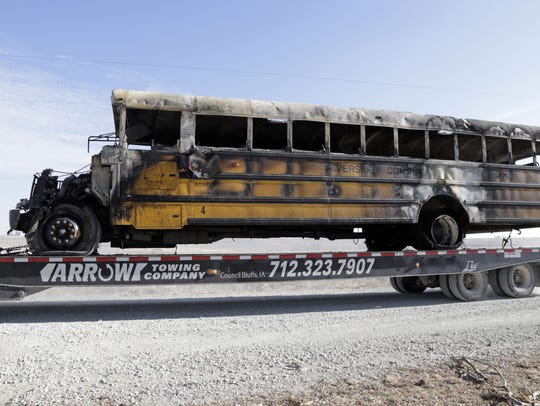 A burned school bus is transported by trailer near Oakland, Iowa, Tuesday, Dec. 12, 2017. A fire aboard the school bus killed a student and the bus driver.