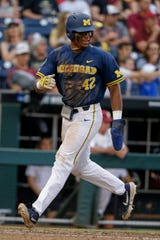 Michigan's Jordan Nwogu scores against Florida State on a single by Jimmy Kerr in the fifth inning of an NCAA College World Series baseball game in Omaha, Neb., Monday, June 17, 2019.
