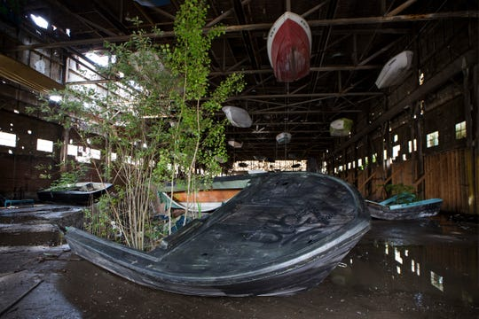 """Bone Black"" is an installation in progress by Scott Hocking in a 25,000 square-foot former industrial building. It uses boats abandoned throughout the city as a suspended fleet in Detroit, Mich., Monday, June 18, 2019."