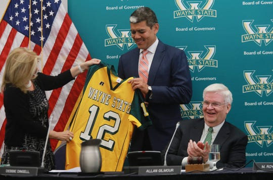 M. Roy Wilson is handed a Wayne State University football jersey while being welcomed as the 12th president for the University by Debbie Dingell and retiring president Allan Gilmour following a special board meeting on Wednesday June 5, 2013 at the McGregor Memorial Conference Center at Wayne State University in Detroit.