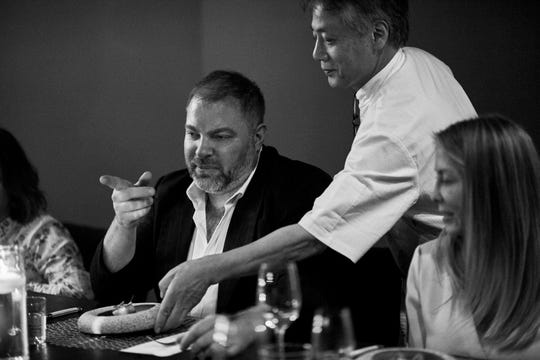 Pernoi Executive Chef Takashi Yagihashi serves a course of Copper River salmon to Detroit Foundation Hotel Executive Chef Thomas Lents at a preview dinner for Yagihashi's upcoming Birmingham restaurant with Luciano DelSignore on June 12, 2019.