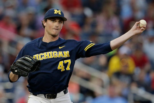 Michigan starting pitcher Tommy Henry throws to first in a pickoff attempt in the fifth inning of an NCAA College World Series baseball game against Florida State in Omaha, Neb., Monday, June 17, 2019.