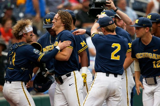 Michigan's Jesse Franklin, center left, is greeted at the dugout after he hit a solo home run against Florida State in the first inning of an NCAA College World Series baseball game in Omaha, Neb., Monday, June 17, 2019.