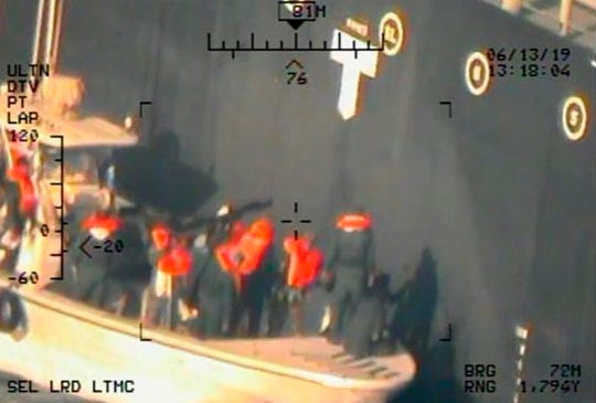 This image taken from a U.S. Navy helicopter, shows what the Navy says are members of the Islamic Revolutionary Guard Corps Navy removing an unexploded limpet mine from the M/T Kokuka Courageous.
