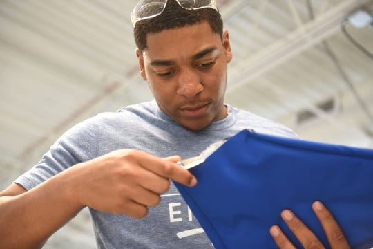 Lions rookie player Anthony Pittman works on the finishing touches of his coat pocket.