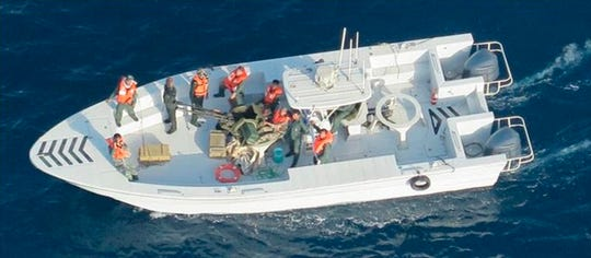 This image taken from a U.S. Navy helicopter, shows what the Navy says is the Islamic Revolutionary Guard Corps Navy after removing an unexploded limpet mine from the M/T Kokuka Courageous.