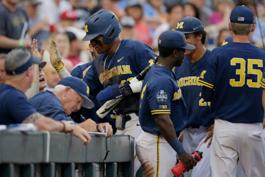 Michigan's Jordan Nwogu, center, is greeted at the dugout after he scored on a single by Jimmy Kerr in the fifth inning Tuesday night against Florida State in the College World Series.