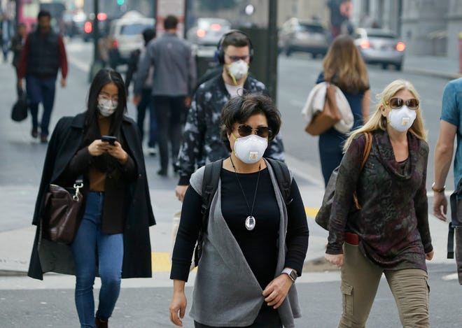 In this Friday, Nov. 9, 2018 file photo, people wear masks while walking through the Financial District in the smoke-filled air in San Francisco, as authorities issued an unhealthy air quality alert for parts of the San Francisco Bay Area as smoke from a massive wildfire drifts south.