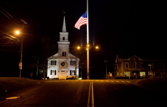 A flag flies at half-staff on Main Street in 2012 in honor of the 26 students and staff killed in a mass shooting at the Sandy Hook Elementary school in Newtown, Conn.