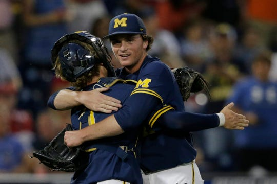 Michigan pitcher Tommy Henry, right, is hugged by catcher Joe Donovan after pitching a complete game against Florida State.