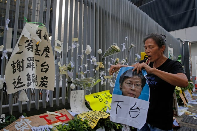 A protester shouts slogans demanding Hong Kong Chief Executive Carrie Lam to step down outside government office in Hong Kong, Tuesday, June 18, 2019. Lam apologized Tuesday for an unpopular extradition bill that drew massive protests.
